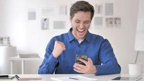 Hombre adulto casual que celebra éxito en Smartphone almacen de metraje de vídeo