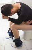 Hombre adulto con el asiento de inodoro que se sienta doloroso de la diarrea Imagen de archivo