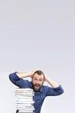 Hombre adulto de la barba del estudiante con la pila de libro en una biblioteca Foto de archivo libre de regalías