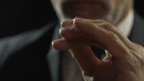Hombre adulto en las lentes que hacen que la mano engaña con la moneda, pensando en presupuesto almacen de metraje de vídeo