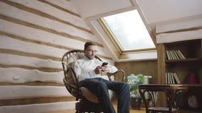 Hombre adulto en los vidrios que practican surf Internet en smartphone en el ático almacen de video
