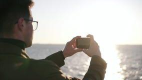 Hombre adulto en ropa elegante usando el teléfono móvil mientras que paseo de la mañana en la playa del mar, tomando una foto de  almacen de video