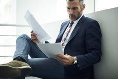 Hombre adulto en una chaqueta y los vidrios que buscan la información para proporcionar servicio jurídico y la consulta que anali imágenes de archivo libres de regalías