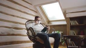 Hombre adulto en vidrios que lee un libro y que bebe el café en el ático almacen de video