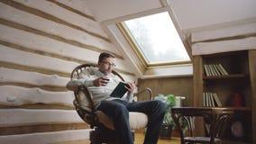Hombre adulto en vidrios que lee un libro y que bebe el vino en el ático metrajes