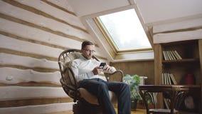 Hombre adulto en vidrios usando el teléfono móvil en el ático almacen de video