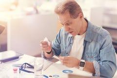 Hombre adulto enfermo que lee las instrucciones en las medicinas Fotos de archivo