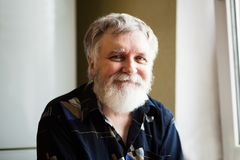 Hombre adulto feliz con el pelo gris que mira en la cámara y la sonrisa imagenes de archivo