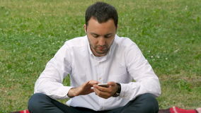 Hombre adulto hermoso que envía un mensaje de texto usando el teléfono celular en la igualación soleada al aire libre en parque almacen de video