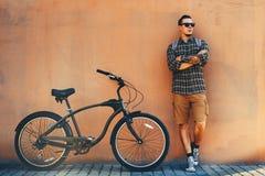Hombre adulto hermoso que se coloca con la bicicleta cerca de concepto rutinario diario de la forma de vida de la pared imagen de archivo