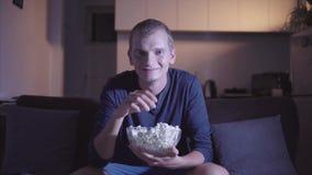 Hombre adulto interesado que mira la TV y el asiento de la película en el sofá cómodo y que come las palomitas sabrosas en cuenco almacen de video