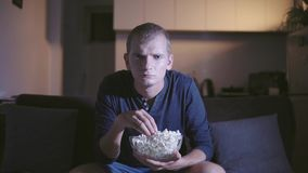 Hombre adulto interesado que mira la TV y el asiento de la película en el sofá cómodo y que come las palomitas sabrosas en cuenco metrajes