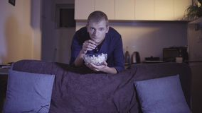Hombre adulto interesado que mira la TV y la película que se colocan cerca del sofá cómodo y que comen las palomitas sabrosas en  almacen de video