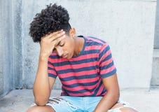 Hombre adulto joven afroamericano triste y pobre Imagen de archivo libre de regalías