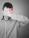 Hombre adulto joven con el punto rojo del dolor de cabeza Foto de archivo