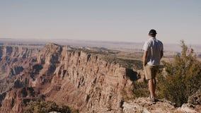 Hombre adulto joven emocionado feliz sorprendente por panorama soleado épico del verano del parque nacional famoso de Grand Canyo almacen de metraje de vídeo