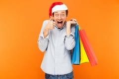 Hombre adulto joven en el sombrero de la Navidad, sosteniendo bolsos coloridos después Fotos de archivo libres de regalías