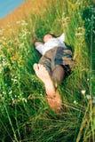 Hombre adulto joven en hierba del resorte fotografía de archivo