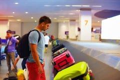 Hombre adulto joven, equipaje que espera del pasajero para en terminal de aeropuerto Foto de archivo libre de regalías