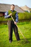 Hombre adulto joven feliz con la incapacidad que trabaja en jardín de la primavera Foto de archivo