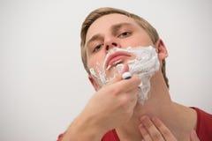 Hombre adulto joven feliz que afeita su cara Imagen de archivo libre de regalías