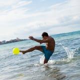 Hombre adulto joven feliz que juega la pelota de playa en verano Fotografía de archivo