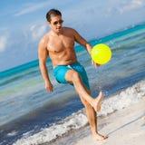 Hombre adulto joven feliz que juega la pelota de playa en verano Fotos de archivo
