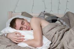 Hombre adulto joven hermoso que duerme en cama El individuo atractivo está descansando fotografía de archivo