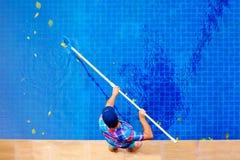 Hombre adulto joven, personal que limpia la piscina de las hojas Imágenes de archivo libres de regalías