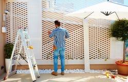 Hombre adulto joven que construye la pared de madera de la pérgola en zona del patio del tejado imagenes de archivo