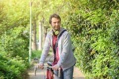 Hombre adulto joven que monta una bici en la ciudad Foto de archivo libre de regalías