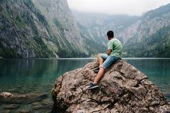 Hombre adulto joven que se sienta en la roca que mira l hermoso y brumoso Fotografía de archivo