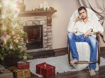 Hombre adulto joven que se sienta en una mecedora en la Navidad internacional Foto de archivo libre de regalías
