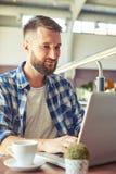 Hombre adulto joven que trabaja con el ordenador portátil en café Imagenes de archivo