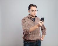 Hombre adulto joven que usa el teléfono móvil Imagen de archivo libre de regalías