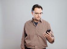 Hombre adulto joven que usa el teléfono móvil Fotos de archivo libres de regalías