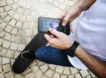 Hombre adulto joven que usa un uso de la música del smartphone al aire libre Foto de archivo libre de regalías