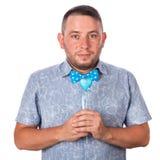 Hombre adulto lindo con una barba en una corbata de lazo azul en camisa del verano con un corazón en manos en un fondo blanco ais Imagen de archivo libre de regalías