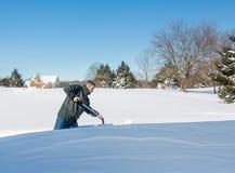 Hombre adulto mayor que intenta excavar la impulsión en nieve Imagenes de archivo