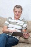 Hombre adulto mayor que trabaja con el nuevo ordenador de la tablilla Foto de archivo libre de regalías