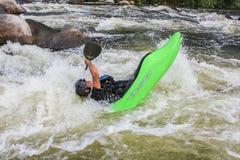 Hombre adulto que bate un kajak en el río fotografía de archivo