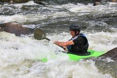 Hombre adulto que bate un kajak en el río imagenes de archivo
