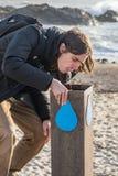 Hombre adulto que bebe de fuente pública de la fuente de agua en la roca arenosa Imagen de archivo libre de regalías