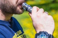 Hombre adulto que fuma un e-cigarrillo del vape en el parque Foto de archivo