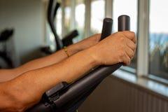 Hombre adulto que hace ejercicio en el gimnasio En la m?quina que hace ejercicio aer?bico imágenes de archivo libres de regalías