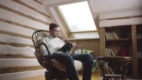 Hombre adulto que lee un libro en el ático metrajes