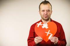 Hombre adulto que lleva a cabo el corazón quebrado Imagen de archivo libre de regalías