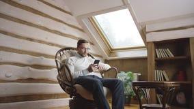 Hombre adulto que manda un SMS en red social en smartphone en el ático almacen de metraje de vídeo