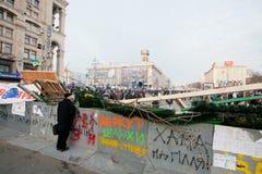 Hombre adulto que mira la demostración en un área rodeada por las barricadas durante la semana de la protesta favorable-europea Foto de archivo libre de regalías
