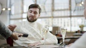 Hombre adulto que paga la cuenta del café con su tarjeta de crédito mientras que se sienta por la tabla con su novia almacen de metraje de vídeo